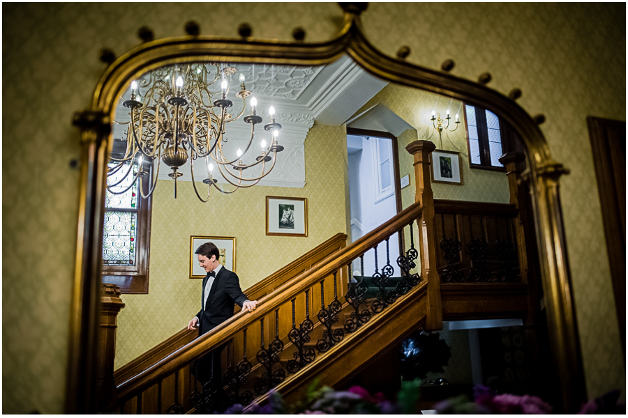 wedding photographer Windsor, groom coming down the stairs with reflection in the mirror